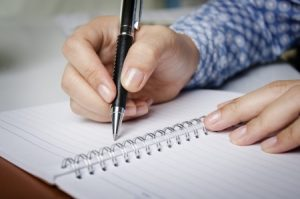 A hand holding a pen is shown writing in a notebook.