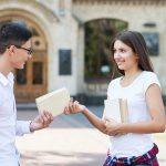 girl giving a book to a guy